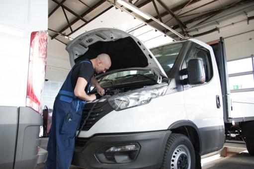 Auszubildender repariert IVECO in der IVECO Partnerwerkstatt schweinfurtMotorhaube geöffenet